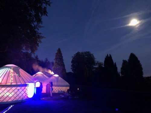 Guests enjoying a party in a collection of Roundhouse Yurts.
